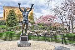 Gonna Fly Now (gabi-h) Tags: statue rocky rockybalboa philadelphia gabih cherrytrees architecture tree fence fencefriday city square moviememories slyvesterstallone character icon stonewall firtree shrubs landscaping park