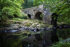 Holne Bridge (Christian Hacker) Tags: stonebridge riverdart longexposure le cokin nd8filter calm granite medieval historic ancient dartmoor nationalpark devon gradeiilisted architecture arches pillars water woodland forest landscape canon eos50d tamron 1750mm riverbank outdoors nature scenic tranquil reflections mirrored dark rocky flow trees tree holnebridge