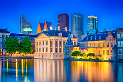 Travel Ideas. Binnenhof Palace of Parliament in The Hague in The Netherlands at Blue Hour. Against Modern Skyscrapers. (DmitryMorgan) Tags: binnenhof gollandia gollandiya haag hague holland netherlands architecture bluehour buildings denhaag dusk dutch europe evening fountain government governmental historic hofvijver hollander kingdomofthenetherlands lights mauritshuis newplaces night places pond reflections skies skyline skyscrapers specific towers travellingconcept unique water