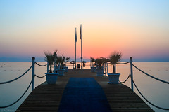 Invitation (Anthony P.26) Tags: category crystaldeluxe kemer places seascape sunrise turkey canon1585mm canon70d canon outdoor travelphotography travel landscapephotography dawn sunglow sky coast coastal sea water calmwater mediterranean deck structure pier wood plants flags