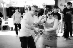 Dancing in the street - revisited (Мaistora) Tags: couple pair man woman male female girl lady emotion mood fun joy motion movement dance rhythm flair elegance style gesture fluid fluent abandon body soul communion primordial street city urban valencia spain glasses shades specs bw bnw blackandwhite mono monochrome analog film silvr paper print grain contrast emulsion look feel vintage reporting journalism action event authentic documentary portrait 90mm sel90m28g sony a6000 lightroom photoshop topaz luminar