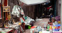 Shop Security (dlerps) Tags: bkk bangkok city daniellerps lerps sony sonyalpha sonyalpha99ii tha thai thailand urban lerpsphotography metropolitan woman alley streetphotography untidy shop market marketstall bottles carlzeiss carlzeissplanar50mmf14ssm planart1450 chinatown