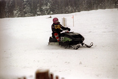 50-352 (ndpa / s. lundeen, archivist) Tags: nick dewolf nickdewolf color photographbynickdewolf 1973 1970s film 35mm 50 reel50 winter maine centralmaine snow snowy snowmobile snowmachine race snowmobilerace racing course fence racecourse finishline ussa racer driver helmet 37 goggles trip wintertrip vacation snowfence bib