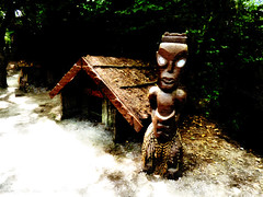 The Maori Guardian (Steve Taylor (Photography)) Tags: maori flaxpiupiuskirt puashells guardian shelter village architecture digitalart house hut brown green yellow white black wooden man newzealand nz southisland canterbury christchurch leaves trees shadow texture spring glow