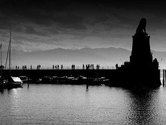 Walking on earth (undefinable moods) Tags: blackwhite bnw monochrome pier dock jetty boats sea water silhouette walk walking people earth seascape skyscape clouds sky lion sculpture reflection tourists line harbour port lindau lake mountains