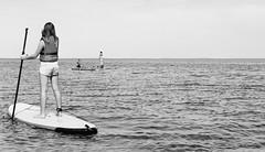 Now look at him! (auqanaj) Tags: hellehansen rettungsweste lifejacket swim swimmer schwimmer schwimmen surfer sportler männer mann mädchen men man girl people kodakgold200 nikonafnikkor50mm114d nikonf100 cewescanat72dpi denmark dänemark ringkøbingfjord hvidesande sup standuppaddling stehpaddeln kopfstand headstand sea lake fjord meer surfbrett surfboard wasser water monochrome blackandwhite schwarzweis urlaub ferien holiday travel journey composition film analog