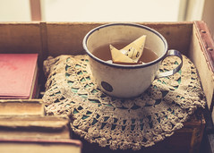 ~Floating to shore...riding a low moon...on a slow cloud. (Fire Fighter's Wife) Tags: paperboat paper tea teacup teatime doily books oldbook vintagebook sunlight sunday vintage vintagestilllife vintageprocessing vintagefeelings 60mm nikon nikond750 sheetmusic cup stilllife sunny lightandshadow lighting box tabletopstilllife tabletop dof depthoffield dreamy dreamscape