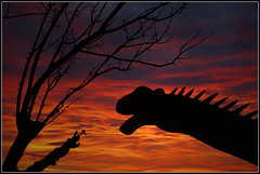 Jurassic Sunset (Jason 87030) Tags: iow island sunset fire sky evening dinosaur silhouette composition tree branch naked roar funny fun amusing creative frame border bright orange red purple glow gold golden capture extinct image flickr tag sony ilce alpha a6000 unusual different everything anything creature prehistoric worls blackgangchine attraction end jurassic park neck necking