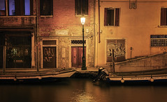 A Venice Beacon (henriksundholm.com) Tags: fondamentadecalabia boat canal water night architecture building lamp light door graffiti tag facade posters advertisement windows hdr venice italy