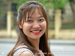 2018-03b Vietnam's Beauty (53b) (Matt Hahnewald) Tags: matthahnewaldphotography facingtheworld people head face eyes mouth teeth lipstick expression lookingcamera smile longhair consent concept living culture lifestyle happiness joy beauty art photoshoot hanoi vietnam asia asian vietnamese southeastasian individual oneperson female adult young woman photography photo detail background nikond3100 primelens nikkorafs50mmf18g 50mm 4x3 horizontal street portrait closeup headshot seveneighthsview sidewaysglance clutteredbackground outdoor color vignette photoshop postprocessing editing posingcamera smiling beautiful pretty lovely cheerful fabulous black clarity