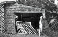 Stacked (Neal3K) Tags: bw blackwhite georgia jchstreetpan400 nikons335mmfilmcamera filmphotographyproject stacking windows shed storage shingles textures