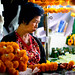 Woman stringing flowers at Warorot Market in Chiang Mai, Thailand