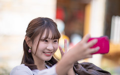 Young woman taking selfie picture with peace sign (Apricot Cafe) Tags: img115159 asia asianandindianethnicities canonef85mmf14lisusm japan japaneseethnicity positiveemotion shibuyaward tokyojapan autumn capitalcities carefree casualclothing charming citylife closeup colorimage copyspace day enjoyment happiness harajukudistrict humanface leisureactivity lifestyles oneperson oneyoungwomanonly outdoors peacesign people photographing photography realpeople selectivefocus selfie smartphone smiling street student sustainablelifestyle toothysmie universitystudent waistup women youngadult