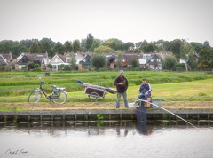 Fishing on the Canal (cheryl strahl) Tags: europe netherlands thenetherlands dutch kinderdijk canal fishing fishingrod bike cart village