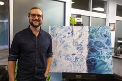 0920 Zack smiles next to his ocean oil painting