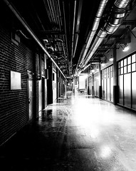 Nordelec hallway (MassiveKontent) Tags: hallway pipes industrial corridor montreal bw contrast city monochrome urban blackandwhite streetphoto metropolis montréal quebec photography bwphotography streetshot architecture shadows noiretblanc blancoynegro building