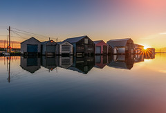 boat houses (Donald L.) Tags: boat house refelction water lake boathouse sunburst sunray