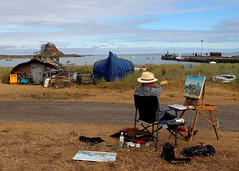 Recording the scene (Paul Brunt) Tags: lindesfarne castle lindesfarnecastle herring boat herringboatshed northernengland northumberland england painter artist coastal coast landscape waterscape blue green grass water land harbour history historic historicmonuments