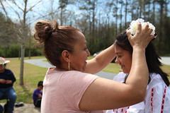 Abila, left, helps Gonzales, right, with her hairpiece. Abila bought almost all of the costumes for her dancers over the past year.