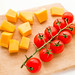 Cubed butternut squash and cherry tomatoes on wooden cutting board on white background