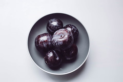 Top view of blue plums in a grey bowl. White background. (wuestenigel) Tags: bio autumn half dessert purple sweet leaf plum two background healthy delicious macro design ripe isolated white single group whole berry closeup drop one wet raw vegetarian blue red fresh ingredient plums element objects cut object water three fruit food organic