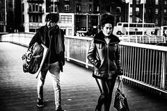 Follow your Muse (Kieron Ellis) Tags: man woman walking bridge bag scarf headphones plasticbag folio artistsfolio traffic contrast candid street blackandwhite blackwhite monochrome
