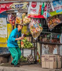 Making a purchase at a sari sari. (FotoGrazio) Tags: elderlywoman market face vendor street shop elderly look travelphotography filipina oldwoman conveniencestore waynesgrazio food waynestevengrazio philippines baguio streetscene woman filipino waynegrazio stare streetphotography business streetvendor fotograzio