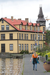 Tjörnin Walk (peterkelly) Tags: digital canon 6d gadventures bestoficeland iceland europe reykjavik tjörnin woman spire yellow building walking water lake red roof