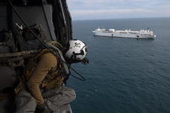 Sailor ensures an MH-60S Sea Hawk helicopter remains clear.