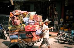 Overload (dlerps) Tags: bkk bangkok city daniellerps lerps sony sonyalpha sonyalpha99ii tha thai thailand urban lerpsphotography metropolitan pulling street working streetphotography pillows man guy cart polstery shopping carlzeissplanar50mmf14ssm carlzeiss planart1450 matress asia