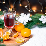 Christmas background with glass of mulled wine, tangerines, Christmas tree and garlands thumbnail