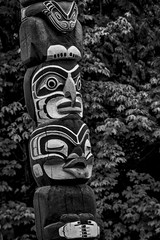 Totem Pole (gecko47) Tags: vancouver stanleypark culturalartifacts bw blackandwhite totempole carving leaves paint figures wood vertical firstnations brocktonpoint kakasolas