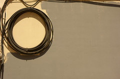 Composizione con cavo arrotolato e muro parzialmente dipinto. Composition with rolled up cable and partially painted wall. (sandroraffini) Tags: abstract reality realtà astratta frammenti urbani urban fragments details dettagli barrio jesus linee curve lines curves light warm grey beige grigio caldo incompleto unfinished wall muro valencia sony rx100 exploration esplorazione cerchio circle cable cavo rolledup arrotolato sandroraffini spagna ombre shadows spain españa detalle abstracción calle strada street pared paret gris amarillo claro minimalismo minimalism explore explored comico funny