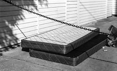 mattress restrained (queue_queue) Tags: bw analog film 35mm biotar zeiss exakta vintagelens vintagecamera sidewalk street mattress discarded chain