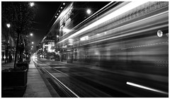 Light trails of a tram driving a street by night (4th Life Photography) Tags: city street tramway light night raod lighttrails publictransportation traffic streetlight rails railway architecture house building exterior artificiallight pavement urbanity urbanview