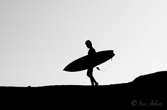 Walking Out (Santa Cruz Pictographer) Tags: surf surfer surfing surfboard board water sea ocean wet splash drops droplets foam wave waves swell swells sets sport sports coast coastal california outside outdoors nature wetsuit crush black white blackandwhite blackwhite bw grey gray greyscale grayscale monochrome silhouette silhouettes minimalist minimal minimalism cliff mountain sky air stark contrast simple hair glasses person portrait