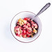 Top view of baked strawberry walnuts oatmeal in a bowl with spoon on white background