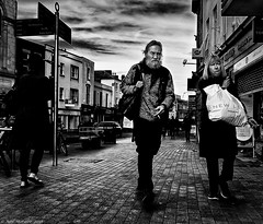 Pushing things to the limit (Neil. Moralee) Tags: neilmoralee street harsh man woman contrast dark taunton candid somerset uk england shopping road walk black white mono monochrome bw bandwblackandwhite neil moralee olympus omd em5 old mature