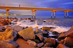 Rocking at dusk (Fnikos) Tags: sea water waterfront mar mare wave seascape landscape pont puente pier bridge people city architecture construction rock sand coast beach shore seashore bay dusk nightfall anochecer sky skyline light cloud outdoor