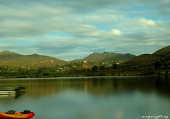 a tranquil moment (forevertide) Tags: lake tranquility longexposurephoto scenery scenicview quietwater movingclouds water mountain hill boat sky landscape calmness kayak wideanglephotography cloudydayphoto scenicsnotjustlandscapes