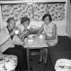 Glamorous lady having a cup of tea in a caravan (vintage ladies) Tags: blackandwhite vintage people photograph 60s female woman lady 60slady 60swoman 60sstyle ladies women 60sladies 60swomen man male smile smiling legs sexylegs skirt sitting watch dress portrait