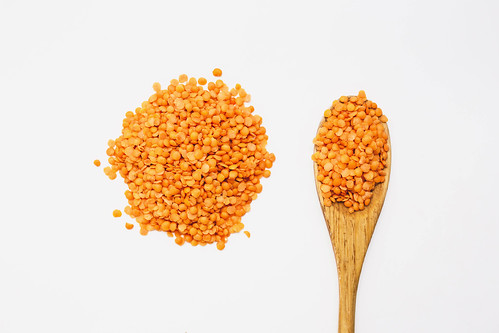 Top view of red lentils on a wooden spoon on white background