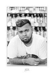 Anybody thirsty..? (AnthonyCNeill) Tags: man mann homme hombre handsome shop keeper offlicence liquor store portrait retrato face black white blanco negro schwarzweiss mono monochrome nikon fm2n 105mm f25 schwarzweis bokeh shallowdepthoffield dof film ilford hp5