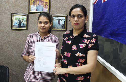 Ms. Parwinder Kaur (Director of West Highlander) handing over Australia Student Visa to Charanpreet Kaur