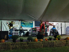 Carla & Redemption On Stage. (dccradio) Tags: lumberton nc northcarolina robesoncounty tent entertainmenttent carlaandredemption carlaredemption gospelmusic gospelnight southerngospel stage instruments musicians sing singing singers flower floral flowers mum mums flag americanflag usa usflag unitedstatesflag oldglory drums drummer speakers keyboard keys hay straw bales pumpkins fall autumn canon powershot a3400is robesonregionalagriculturalfair fair countyfair robesoncountyfair fun entertainment communityevent