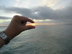 holding on to sunset (kenjet) Tags: beach hawaii ocean pacific oahu waikiki waikikibeach pacificocean sand wave waves paradise watch pinch sun pm evening sunset setting fingers arm