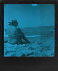 She enjoyed the sun (ale2000) Tags: polaroidweek polaroid analog analogue instant instantphotography impossible slr680 600 duochrome blue blu black nero square frame blackframe roidweekfall2018 leisure summer beach beachtime beachporn spiaggia mare sand sabbia candid woman azzurro
