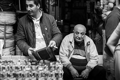 look into my eyes, and speak the truth / the eyes of the city (Özgür Gürgey) Tags: 2018 50mm bw d750 eminönü nikon candid eyecontact grainy marketplace people sitting street istanbul