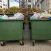 Große grüne Mülltonnen voll bis oben hin in einer Wohngegend