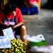 Woman selling oranges at Warorot Market in Chiang Mai, Thailand
